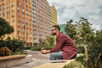 Wall Mural - Great weekend. Side view of handsome man with stubble in casual clothes drinking coffee while sitting on the bench outdoors