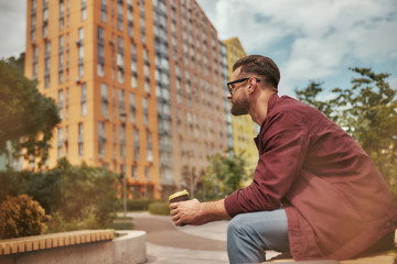 Wall Mural - Relaxing. Side view of handsome man with stubble in casual clothes drinking coffee while sitting on the bench outdoors