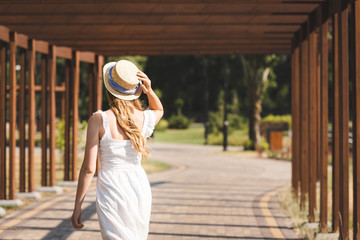 Wall Mural - back view of girl in white dress touching straw hat while walking on pathway near wooden construction