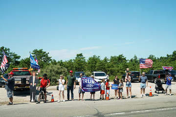 People line the streets as U.S. President Donald Trump's motorcade arrives for a fundraising luncheon to benefit his reelection campaign and the Republican National Committee in Southampton