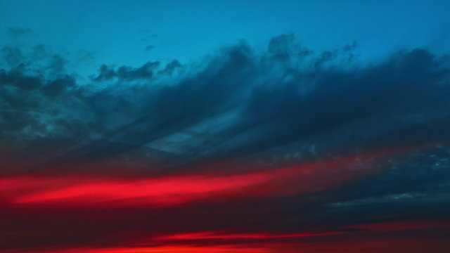 Colorful Red Glow On A Dark Cloudy Dramatic Sky