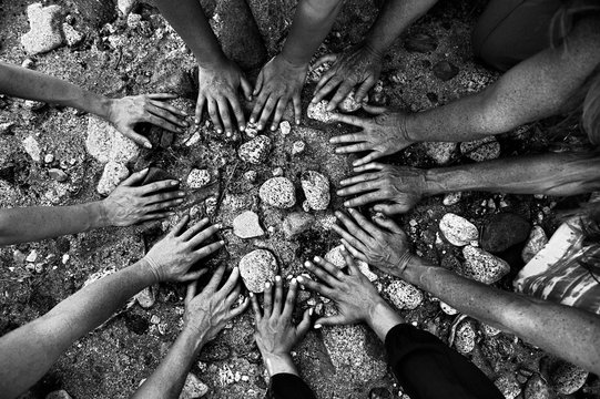 Women's gathering hands all coming together in a circle in nature..