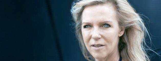 Attraktive reife Frau mit blonden Haaren und strahlenden blauen Augen