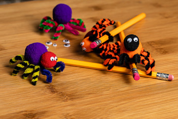 Fun Halloween Crafts.  Spiders made of pom poms and pipe cleaners.  Attach to pencils.