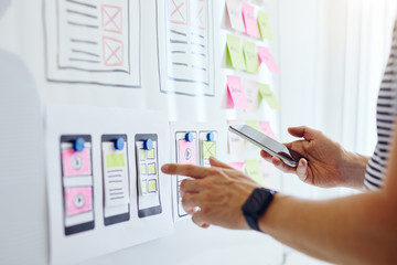 Web developer with mobile phone planning website ux app development on white board