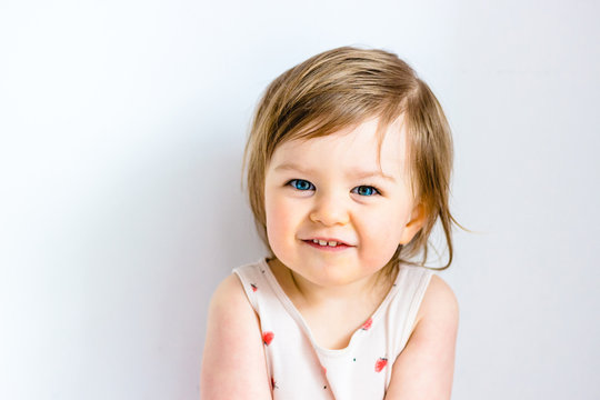 Happy smiling funny toddler child girl on white background
