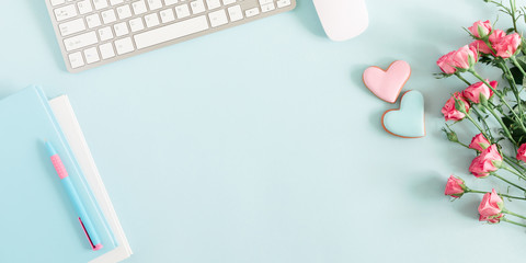 Composition Valentine's Day. Keyboard, notepad, rose flowers, ginger cookie in shape heart on pastel blue background. Valentine day concept, design. Flat lay, top view, copy space