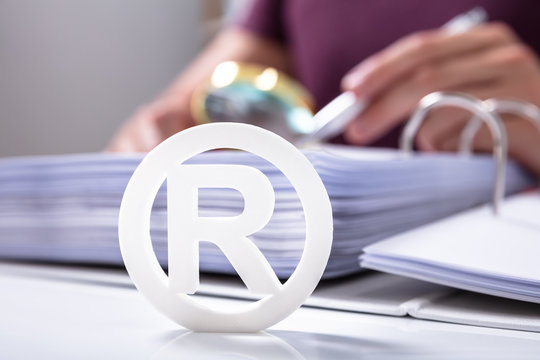 White Registered Trademark Sign Near Documents