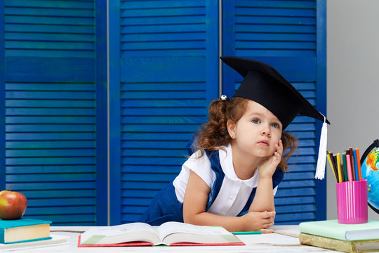 Smart toddler kid. Back to school. Cute industrious child girl in graduation cap is sitting at a desk indoors. Kid is learning in class on background of blue wall. Girl reading the book