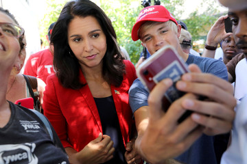 2020 Democratic U.S. presidential candidate Tulsi Gabbard takes a selfie with a fairgoer wearing a Trump 2020 hat at the Iowa State Fair in Des Moines