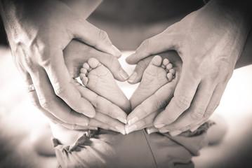 Eltern formen Herz um Babyfüße, sepia