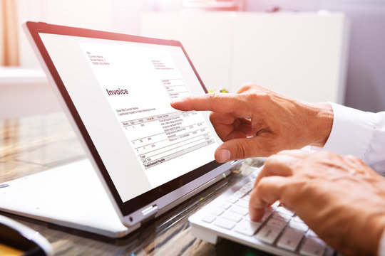 Businessman's Hands Working On Invoice On Laptop
