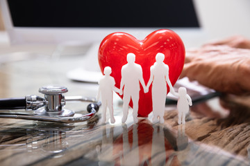 Heart With Family In Front Of Doctor Working On Computer