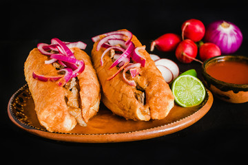 tortas ahogadas, traditional Mexican Food from Jalisco Guadalajara Mexico, spicy sandwich in a red...