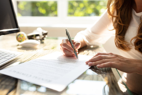 Businesswoman's Hand Signing Contract With Pen