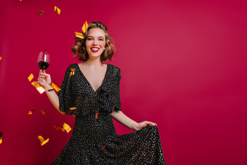 Blissful female model with shiny curly hair posing with wineglass on claret background. Emotional young woman wears black attire having fun at party with champagne and confetti and smiling.