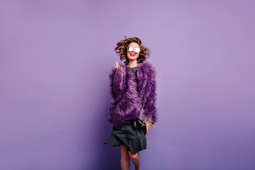 Stunning girl in good mood jumping on purple background and smiling. Studio shot of spectacular woman in fluffy winter clothes having fun on photoshoot.