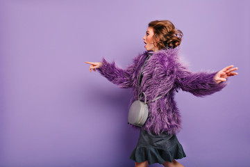 Fascinating trendy woman with elegant purse dancing on purple background. Indoor photo of pleased young lady in fur coat having fun during studio photoshoot. Wall mural