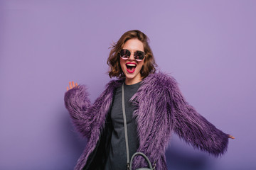 Inspired lady with stylish makeup dancing in purple fur coat and laughing. Indoor portrait of glad lovely woman in soft jacket and dark sunglasses. Fototapete