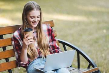 Wall Mural - beautiful girl in casual clothes holding paper coffee cup while sitting on wooden bench in park and using laptop