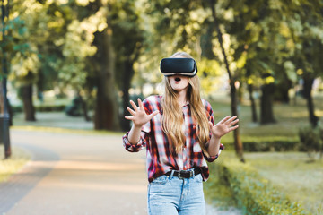 Wall Mural - surprised young girl in casual clothes using vr headset