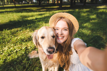 Wall Mural - beautiful young girl in white dress and straw hat hugging golden retriever and taking selfie while sitting on meadow, smiling and looking at camera