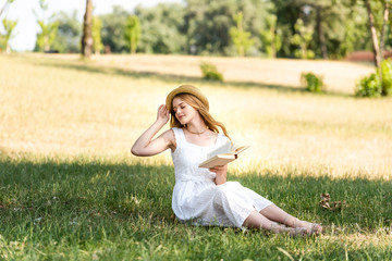 Wall Mural - full length view of beautiful girl in white dress touching straw hat and holding book while sitting on meadow with closed eyes