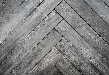 Black rough wooden background, parquet floor herringbone pattern