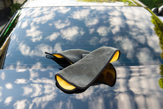 Car towel placed on the car with shiny black colour