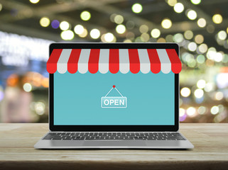 Modern laptop computer with online shopping store graphic and open sign on wooden table over blur light and shadow of shopping mall, Business internet shop online concept