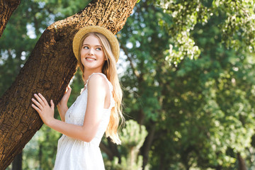Wall Mural - beautiful young girl in white dress and straw hat standing near trunk of tree
