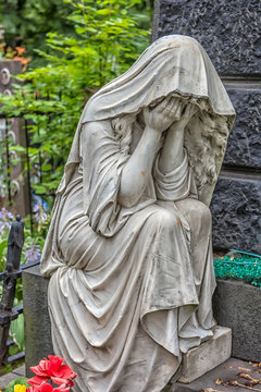 sculpture of a grieving woman on a grave