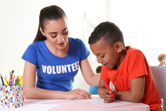 Little African-American boy learning alphabet with volunteer at table indoors