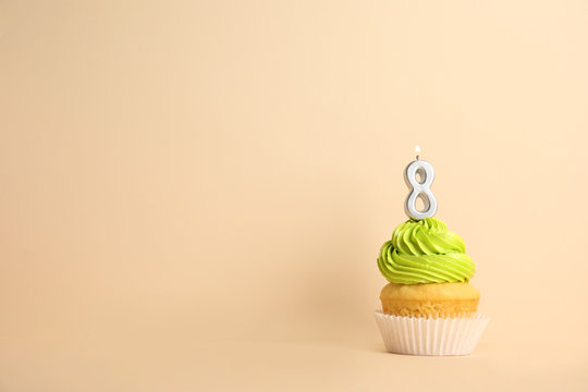 Birthday cupcake with number eight candle on beige background, space for text