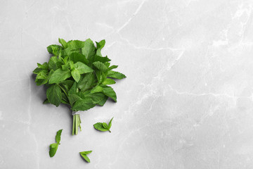 Bunch of fresh mint on grey marble  background, top view. Space for text
