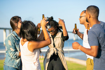 Happy young people dancing with raised hands. Group of friends relaxing in park during sunset. Leisure concept Wall mural
