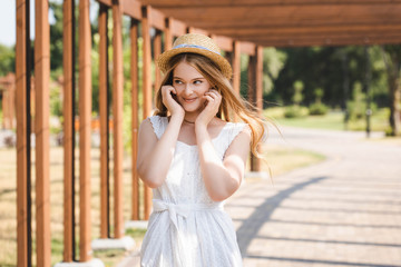 Wall Mural - beautiful girl in white dress and straw hat smiling and looking away
