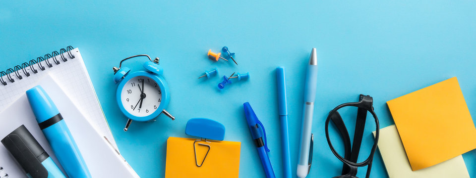 back to school or office styled scene with multicolored school supplies on blue , back to school conceptual background flat lay long banner.