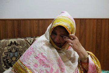 Amna Altaf, whose parents and siblings are living in the Indian-administered Kashmir, and are unable to contact due to the Internet and mobile networks shutdown, reacts at her home in Muzaffarabad