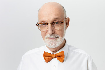 Aging, maturity and people concept. Picture of serious senior man with thick beard and bald head frowning eyebrows, being in bad mood because of headache, posing isolated at copyspace studio wall