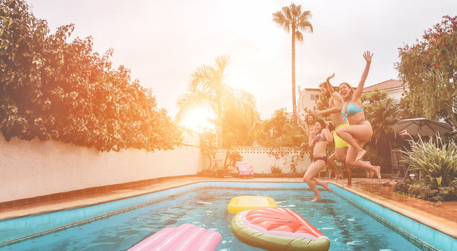 Happy friends drinking jumping in swimming pool at sunset - Young  people having fun in tropical vacation - Summer holiday, youth and friendship concept - Soft focus on close-up girl