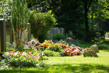 Friedhof - blumenbedecktes Grab