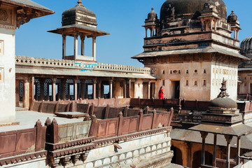 Woman in red sari walling on the 17th century Citadel of Jahangir with towers and arches, India. Fort in Orchha city, indian state Madhya Pradesh