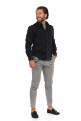 Handsome Man In Gray Trousers, Moccasins And Black Shirt Is Standing And Looking Away