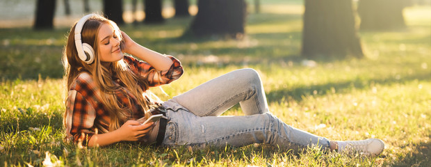 Wall Mural - panoramic shot of beautiful girl in casual clothes lying on meadow in sunlight and listening to music on headphones