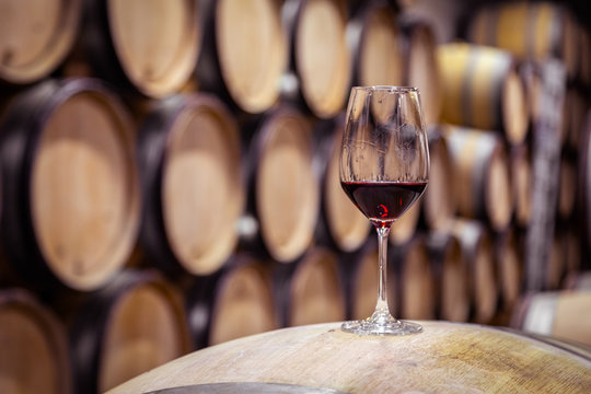 Closeup glass with red wine on background wooden wine oak barrel stacked in straight rows in order, old cellar of winery, vault. Concept professional degustation, winelover, sommelier travel