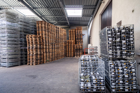 Large warehouse at the factory, winery, bottles of wine in metal baskets ready for transportation, piles of wooden pallets. Concept importer wine, merchant