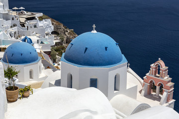 Greece. Cyclades Islands - Santorini (Thira). Oia town with typical Cycladic architecture - painted blue cupolas and white walls of houses. The Anastasis Church.