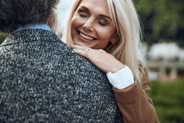 Delighted woman hugging man and laughing stock photo