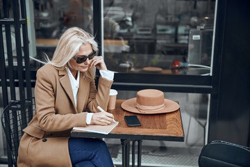 Mature woman making notes in cafe stock photo